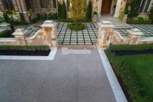 Residential Driveway receives Bomanite Exposed Aggregate Deep Washed Sandscape Texture System with a Buckskin Integral Color to Complement the Extravagant Courtyard, Basketball Brick Court and Stone Columns and Walls installed by Bomanite Toronto to withstand the Canadian Winters.
